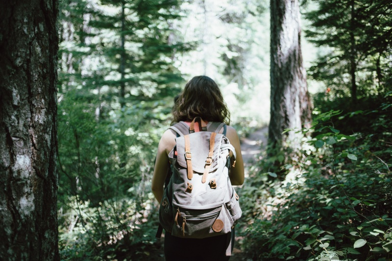 woman with a backpack on a hiking trail in the woods
